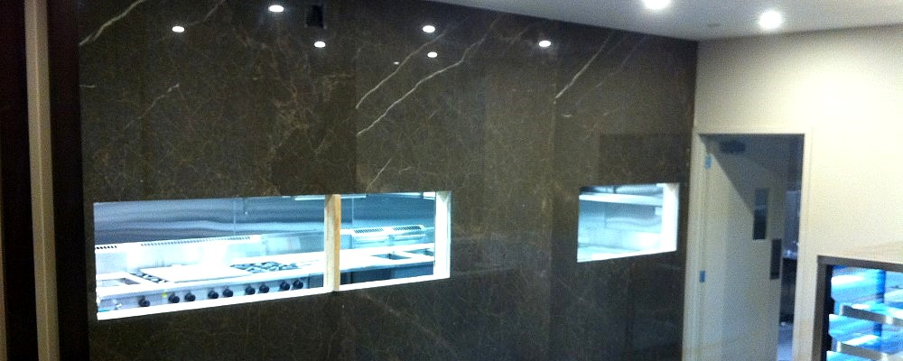 Black Stone Wall with Window Cutouts to Commercial Kitchen